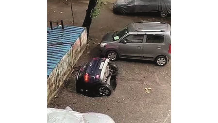 Carro engolido por buraco