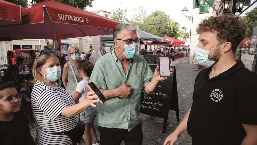 Clientes exibem certificado digital à entrada de um restaurante em Lisboa