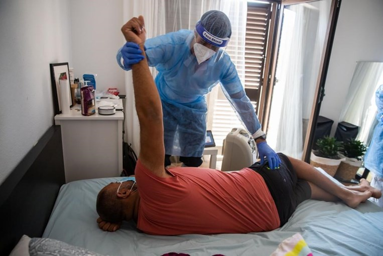 Enfermeiro da Unidade de Hospitalização Domiciliária do Hospital Garcia de Orta, Filipe Dias, ensina exercícios respiratórios a Jair, um paciente internado em casa com Covid-19, na zona do Seixal