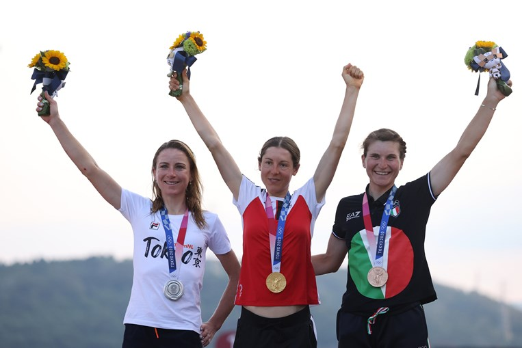 A medalha de ouro Anna Kiesenhofer da Áustria comemora no pódio com a medalha de prata, Annemiek van Vleuten da Holanda e a medalhista de bronze, Elisa Longo Borghini, da Itália