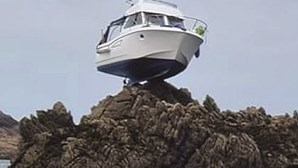 Barco fica 'pendurado' em rochedo