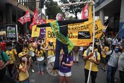 Manifestantes contra Bolsonaro levam cartazes com mensagens de protesto e apelidam o presidente de 'genocida'